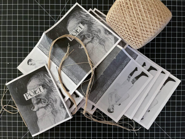 Unbound zine pages prepared for binding with thread
